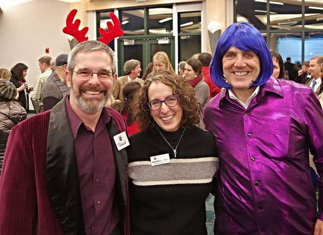 three adults posing with wig and antlers