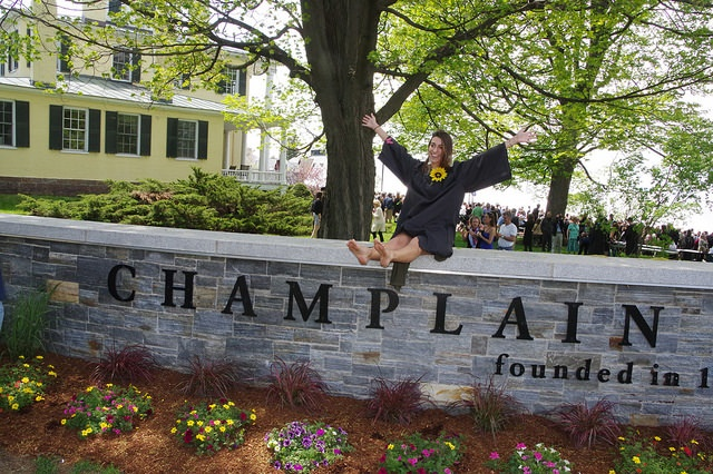 A Champlain College Class of 2016 graduate sits on the Champlain College sign with a sunflower